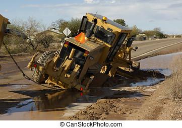 Stuck Grader - A road grader machine stuck in the mud along...