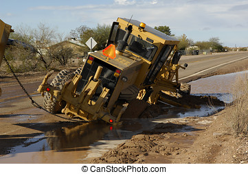 Stuck Grader - A road grader machine stuck in the mud along...