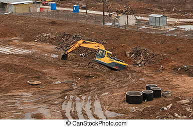 Stuck in the mud at the construction site excavator yellow