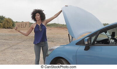Stuck with car African American model with help sign