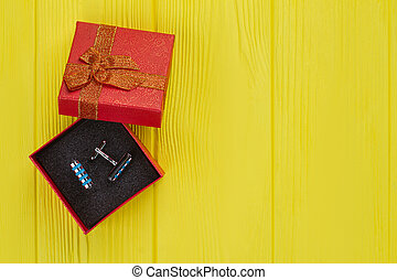 Stud buttons in red opened gift box.