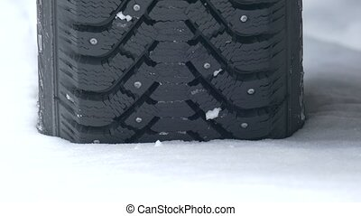 Studded tyre in snow - Studded car winter tyre driving away...
