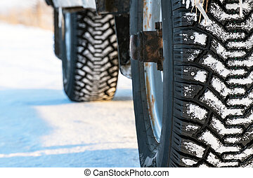 Studded winter car tires on winter road