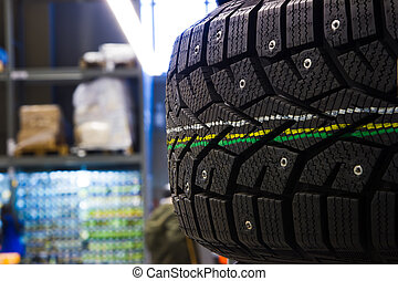 New modern studded winter tires on the shelf in the store