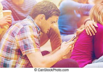 studenci, uśmiechanie się, smartphone, grupa