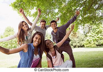 studenci, zewnątrz, przedstawianie, uśmiechnięty szczęśliwy