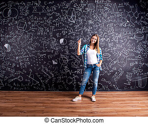 Student against a big blackboard with mathematical symbols -...