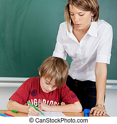 Student and teacher at school during lesson