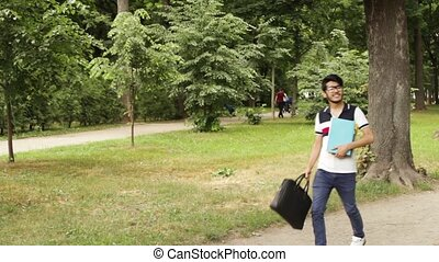 Student asian man walking in the park in summer day