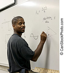 A handsome african-american student at the board doing trigonometry.
