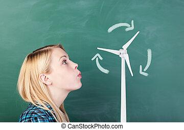 Student Blowing On Wind Turbines Drawn On Chalkboard