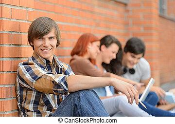 Student boy friends sitting in background