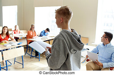 student boy with notebook and teacher at school