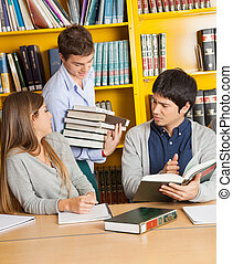 Student Carrying Books While Friends Sitting In Library