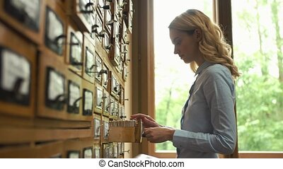 Student checks cards with books' names in the library