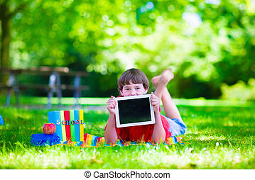 Student child with tablet computer in school yard