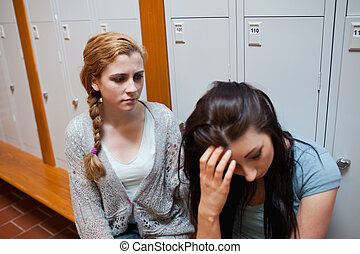 Student comforting her friend while sitting on a bench