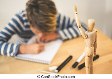 Student drawing with pencil a human figure be inspired by a wooden model. Boy copying a dummy for school art tasks. Kid hold a pencil and draw a manga at home. Education, talent and ability concept.