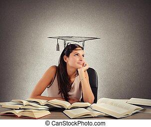 Student dreams graduation - Young student between books...