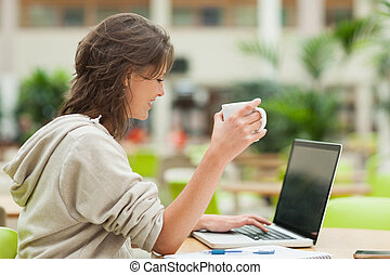 Student drinking coffee while using laptop at cafeteria...