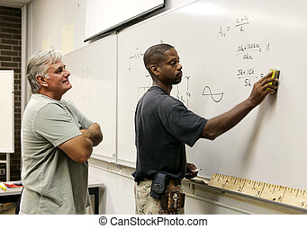 Student Erasing Board - A teacher looks on as his adult...