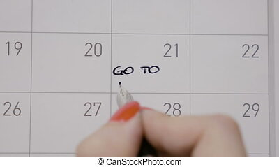 Student female hands writing with black pen on calendar go to pilates with capital letters