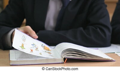 Student flips the pages of the textbook. Close up