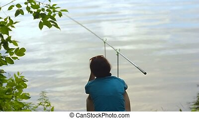 student girl fisherman is fishing on the bank of the river, lake