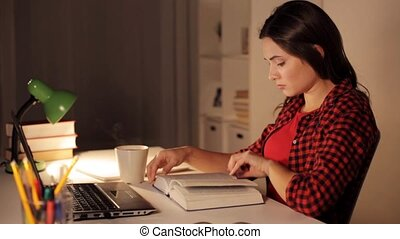 student girl or woman reading book at night home - people,...