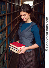 Student girl or woman with books in library.