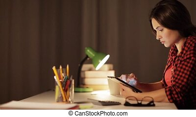student girl or woman with tablet pc at night home -...