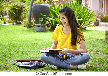 student girl reading a book in park