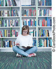 student girl reading book in library