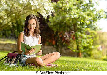 Student girl reading book sitting on grass