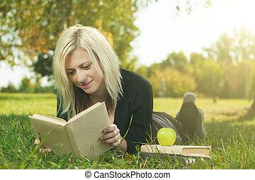 student girl reading on grass