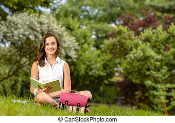 Student girl sitting grass with open book