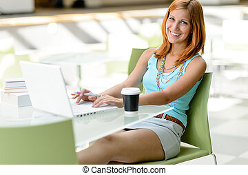 Student girl sitting in assembly hall smiling working on...