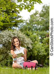 Student girl sitting on grass reading book