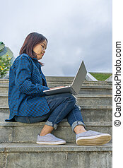 Student girl using laptop, sit on stairs in campus