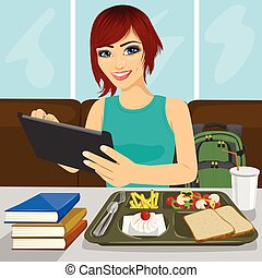 student girl using tablet sitting in fast food restaurant