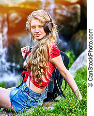 Student girl with backpack headphone listen music on green grass