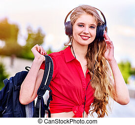 Student girl with backpack in headphone listen music after exam.