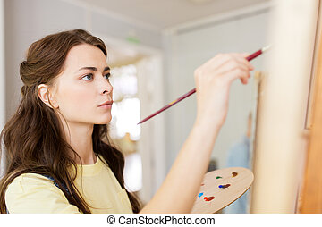 student girl with easel painting at art school - art school...