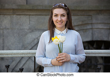 Student girl with flowers in summer day