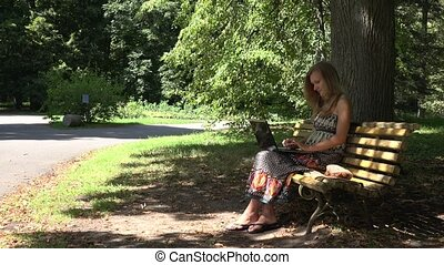 student girl work with laptop sitting on bench in green...