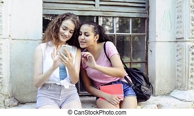 Student girls with smartphone in front of university. -...