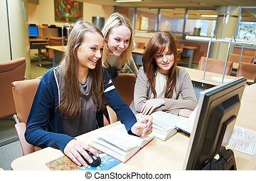 student girls working with computer in library
