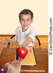 Student giving teacher an apple - A schoolboy hands his...