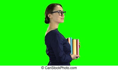Student goes to school with books in her hands. Green screen. Side view