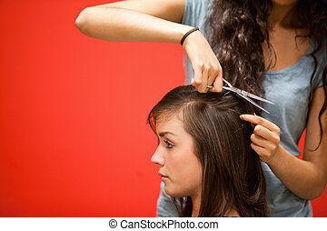 Student hairdresser cutting hair with scissors